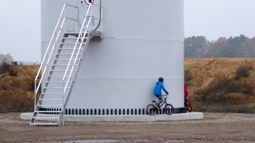Ein Kind umrundet mit dem Fahrrad den Fuß des Windrads