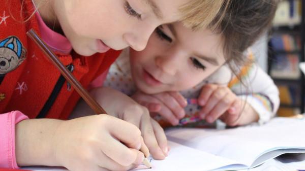 Das Bild zeigt zwei Kinder beim Lernen